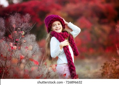 A cute little girl in a knitted hat with a scarf in an autumn forest