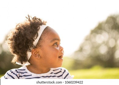 Cute little girl laughing and playing outside.