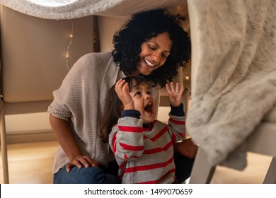 Cute little girl laughing while sitting in a blanket fort with her mother on their living room floor at home