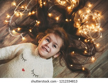 Cute little girl laying on flor with bright christmas garland in her hair. Christmas portrait, cozy style. Top view.