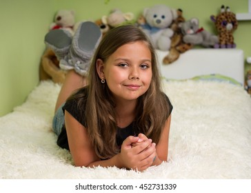 Cute little girl laying on the bed and smiling