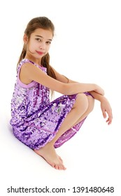 A cute little girl leaned against a white wall. Cyclorama in studio. Isolated on a white background.