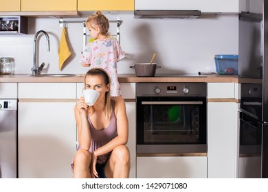 Cute little girl learning cooking with mother in kitchen at home together. Little girl standing on the chair while mother taking brake with a cup of coffee. Concept of family, cooking and food.