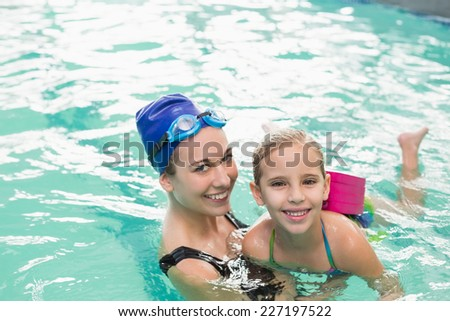3b0f0ebbda Cute little girl learning to swim with coach at the leisure center