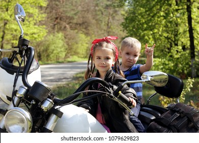 Cute little girl in leather jacket with her small brother making a horns gesture riding the motorbike in the early spring park, family extreme weekend, outdoor portrait, adventures and safety