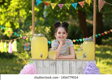 Cute little girl at lemonade stand in park. Summer refreshing natural drink
