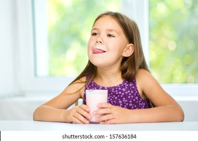 Cute little girl is licking her lips while drinking milk