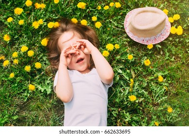 Cute little girl lies on a green lawn with yellow dandelions and covers his face with his hands. Top view, space for text.