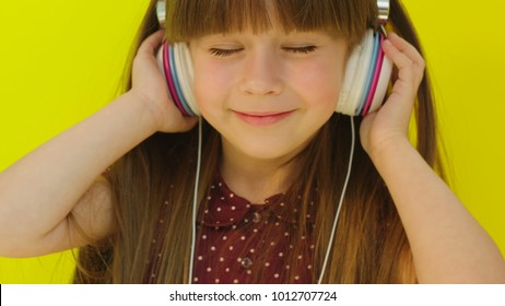 Cute little girl listening to music in white headphones and smiling. Girl moving to the rythm. Yellow wall background. Close up