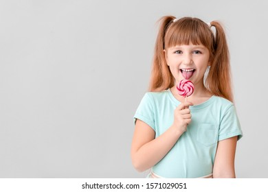 Cute little girl with lollipop on light background