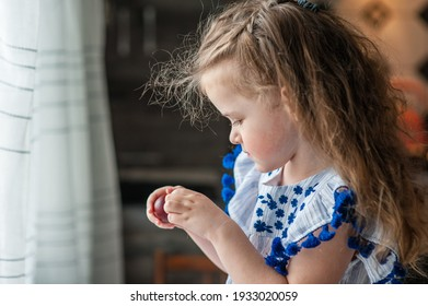 A cute little girl with long curly hair holds Easter eggs in her hands. Portrait. Close-up