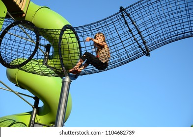 Cute little girl with long hair have a fun on the kid's playground. Summer
