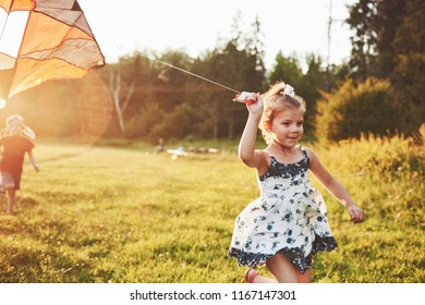 Cute little girl with long hair running with kite in the field on summer sunny day,
