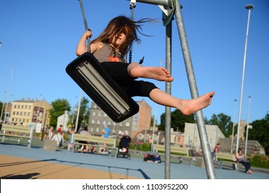 Cute little girl with long haire having fun on swing at playground against the blue sky