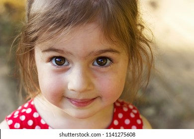 Cute little Girl looking at the camera  surprised. Happy Kid outdoors