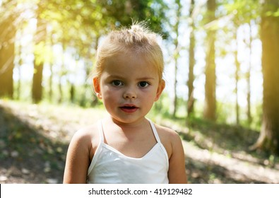 Cute little girl looking at camera and enjoying in the forest.
