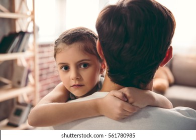 Cute little girl is looking at camera and smiling while hugging her father
