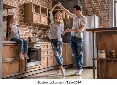 Cute little girl is looking at her beautiful parents dancing, all are smiling while spending time together in kitchen