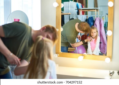 Cute little girl looking in mirror with interest while handsome young makeup artist applying pink lipstick on her lips, interior of messy photostudio on background