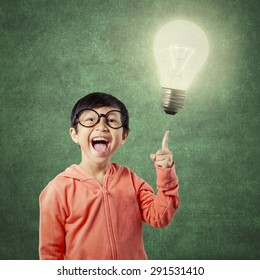 Cute little girl looks have a brilliant idea and pointing at a bright light bulb