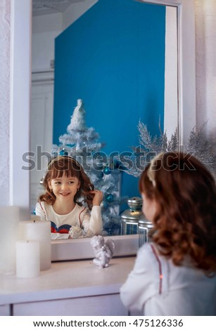 cute little girl looks in the mirror. The concept of the New Year and Merry Christmas