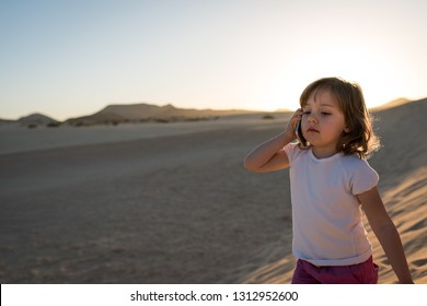 Cute little girl lost in desert - walking on sand dune and making phone call.