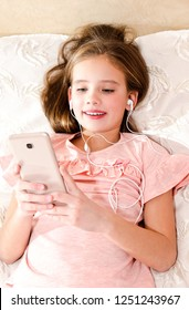 Cute little girl lying on the bed and listening to music using smartphone and listening on headphones earphones
