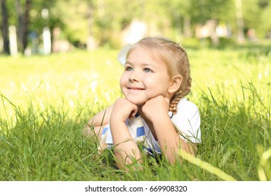 Cute little girl lying on green grass in park