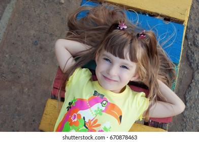 Cute little girl lying on a Park bench