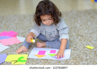 Cute little girl make applique, glues colorful house, applying a color paper using glue stick while doing arts and crafts in preschool or home. The idea for children's creativity, art project.