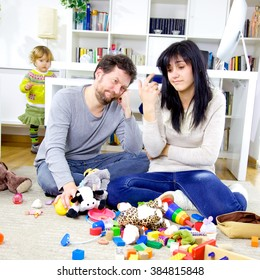 Cute little girl making mess with toys while parents are very tired