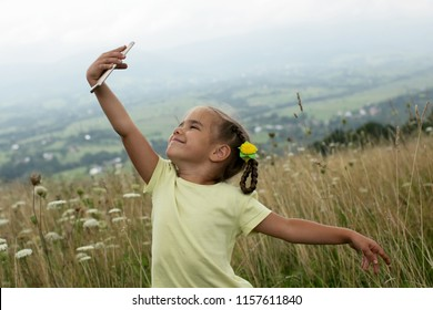 Cute little girl making a photo of beautiful panoramic view in mountains during her vacation and sharing it with her friends on smartphone, summer outdoor, gadget and technology concept