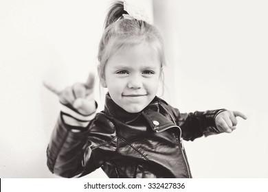 cute little girl making a rock-n-roll sign
