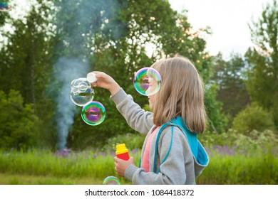 Cute little girl making soap bubbles in a summer park