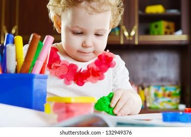 Cute little girl making a star shape from clay dough