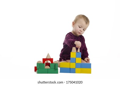 Cute little girl making towers from bricks. Isolated on white