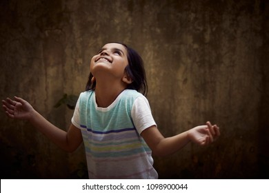 cute little girl making a wish with her arms open