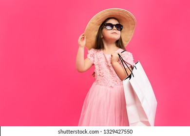 Cute little girl with many shopping bags in dress on pink backgound