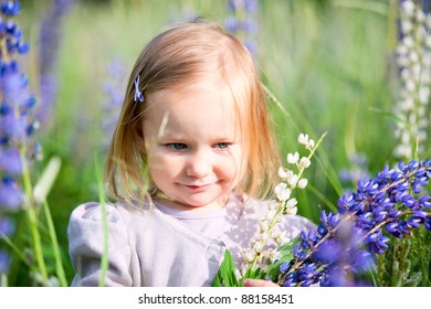 Cute little girl in meadow at sunny summer day
