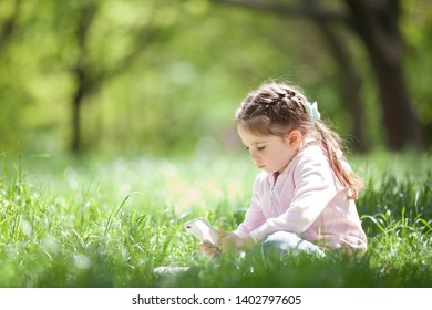 Cute little girl with mobile phone in the park. Family outdoor lifestyle. Happy small sitting on green grass. Beauty nature at summer or spring. Childhood happiness. Mobile children.
