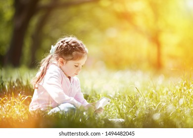 Cute little girl with mobile phone in the fall park. Family outdoor lifestyle. Happy small sitting on green grass. Beauty nature at autumn. Childhood happiness. Mobile children.