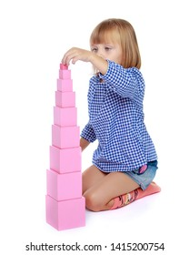 Cute little girl in Montessori in kindergarten working with a pink pyramid.