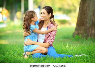 Cute little girl with mother in park on sunny day
