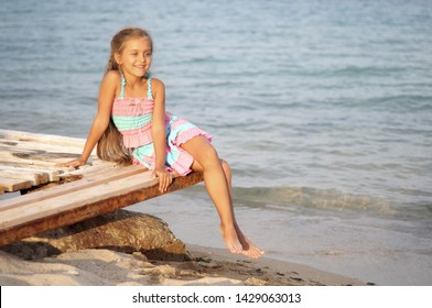 Cute little girl on the beach. Baby is resting near the sea. Summer holidays. Girl in summer. Beautiful little girl lies on pier near water. girl lying on a wooden bench on the beach.