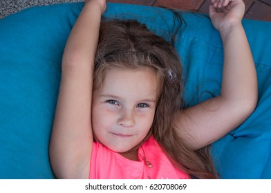 Cute little girl on bean bags, resting, portrait, long hair