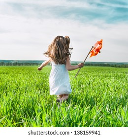 cute little girl on grass in summer day holds windmill in hand
