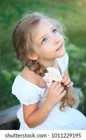 Cute little girl on nature in bright summer day looking up