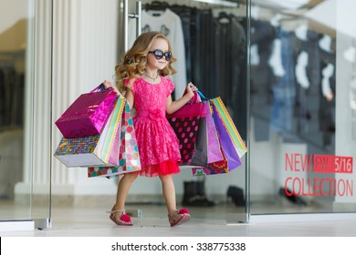 cute little girl on shopping. portrait of a kid with shopping bags. child in dress, sunglasses and shoes near shopping mall having fun. shopping. girl.