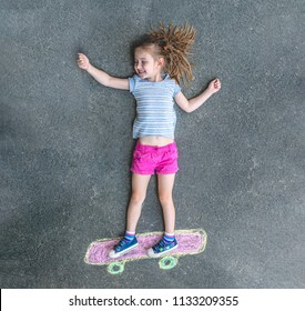 cute little girl on a skateboard drawn in chalk on the pavement. view from above