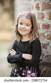 cute little girl in outside setting with arms crossed, smiling